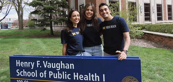 graduating students standing by the school of public health sign