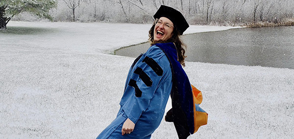 student celebrating graduation in the snow