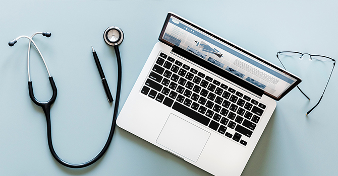 stethoscope, laptop, and glasses sitting on a desk