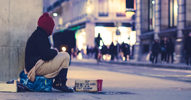 A person, who is presumed homeless, sits on the corner of a street.