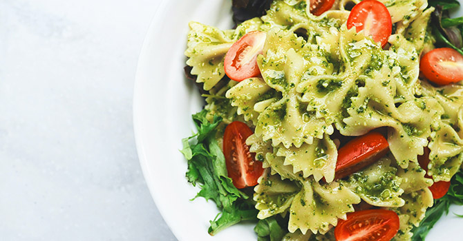 Bowl of bowtie pasta with pesto and tomatoes