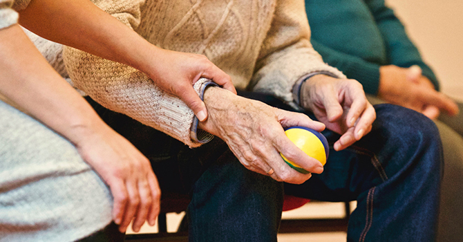 Elderly person holding stress ball