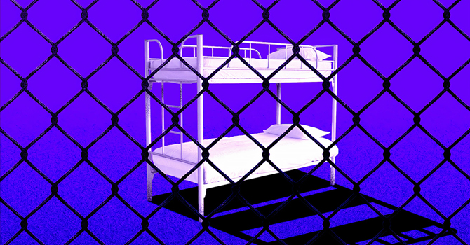 Bunk beds viewed through chain-link fence