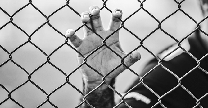 An imprisoned person grips a chain-link fence